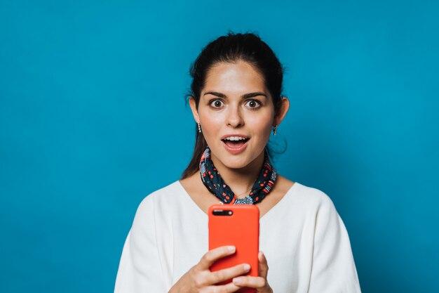 Foto de estudio de mujer bonita mirando al teléfono móvil, se siente sorprendida, abre la boca, vestido con una blusa blanca y pañuelo para el cuello, aislado sobre fondo azul con espacio en blanco para su promoción