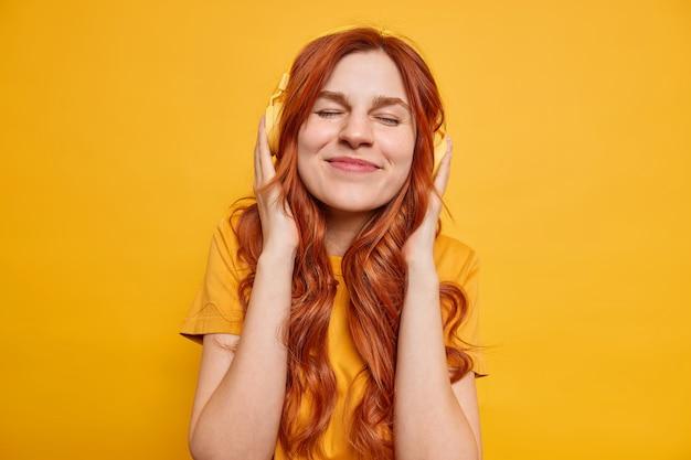 Foto de estudio de mujer complacida con cabello largo y ondulado de jengibre mantiene los ojos cerrados disfruta de una buena calidad de sonido en auriculares escucha su canción favorita