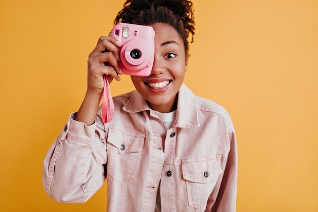 Foto de estudio de mujer emocionada tomando fotos