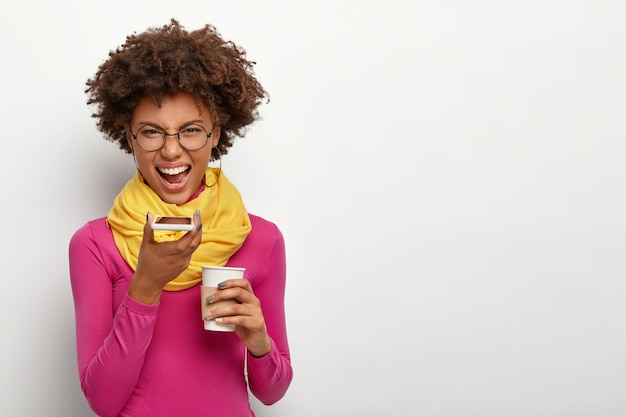 Foto de estudio de mujer enojada e irritada con peinado afro, hace llamadas de voz a través de un teléfono inteligente, bebe café para llevar, usa lentes ópticos, cuello alto rosa y bufanda amarilla, aislado sobre una pared blanca