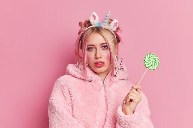 Foto de estudio de mujer europea rubia seria con maquillaje brillante lleva diadema de unicornio y abrigo de piel mira seriamente a la cámara