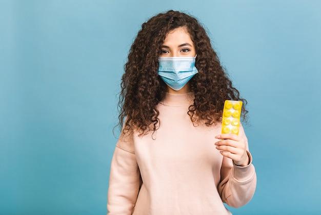 Foto de estudio de mujer infectada con pastillas en las manos, dama con máscara protectora