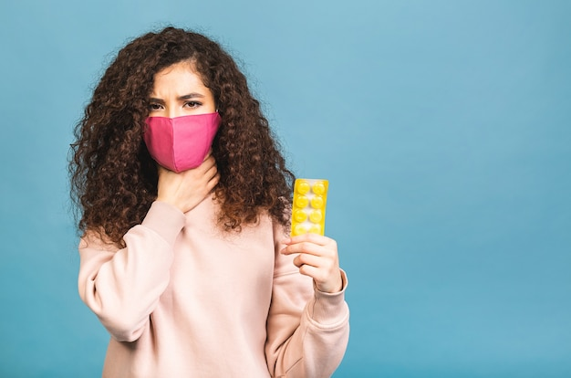 Foto de estudio de mujer infectada con pastillas en las manos, dama con mascarilla protectora, evita la propagación de virus peligrosos