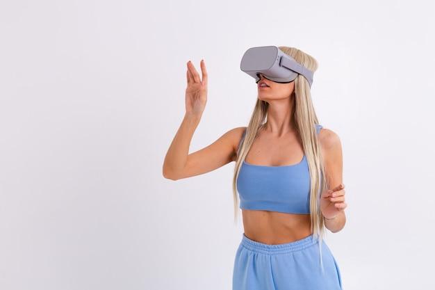Foto de estudio de una mujer joven y atractiva en un traje de moda azul cálido con gafas de realidad virtual sobre un fondo blanco