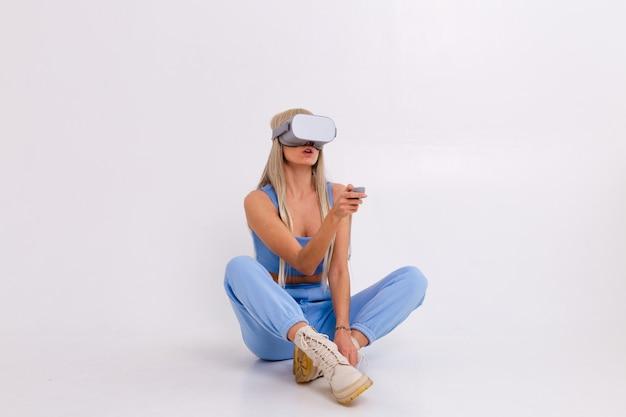 Foto de estudio de una mujer joven y atractiva en un traje de moda azul cálido con gafas de realidad virtual