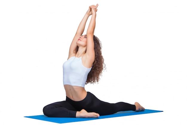 Foto de estudio de una mujer joven en forma haciendo ejercicios de yoga.