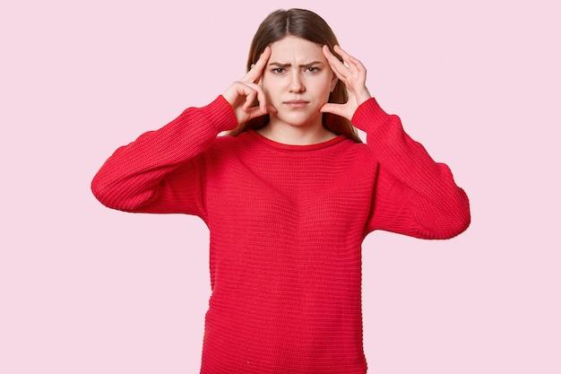 Foto de estudio de mujer morena disgustada sufre de dolor de cabeza