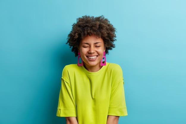 Foto de estudio de mujer positiva con cabello afro mantiene los ojos cerrados, sonrisas de placer, muestra dientes perfectos blancos, usa camiseta verde casual y aretes aislados sobre una pared azul