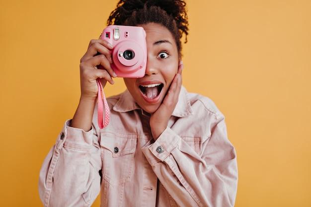 Foto de estudio de mujer sorprendida sosteniendo frente