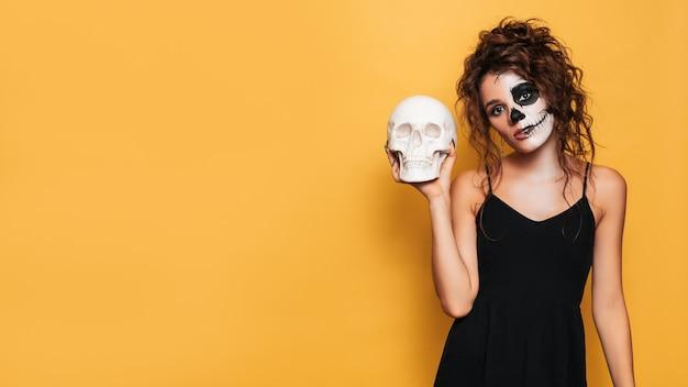 Foto de estudio de una niña con un disfraz de espíritus malignos en una fiesta de disfraces de halloween con una calavera en sus manos. un lugar para su texto para productos, publicidad. el arte de halloween.