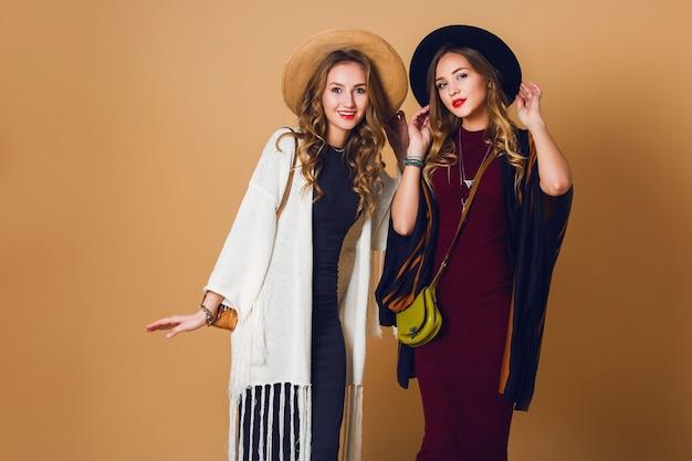 Foto de estudio de otoño de dos modelos con peinado ondulado rubio en lana y sombrero de paja con poncho a rayas