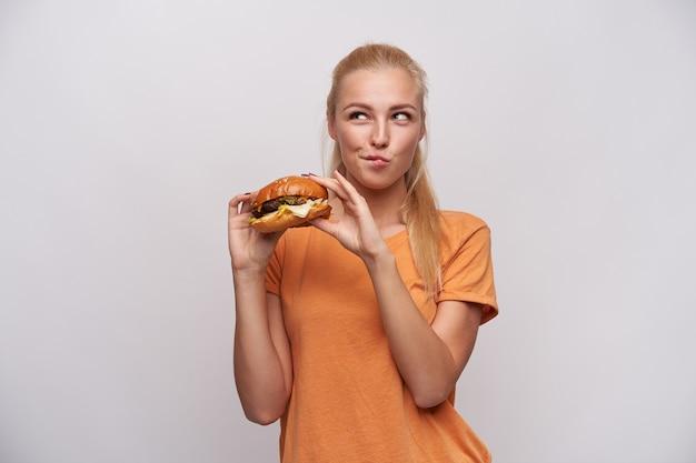 Foto de estudio de positivo joven bastante mujer rubia de pelo largo comiendo hamburguesa fresca y mirando dudosamente a un lado, vestida con camiseta naranja mientras está de pie sobre fondo blanco