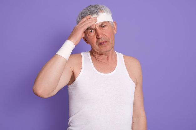 Foto de estudio de senior masculino con dolor de cabeza