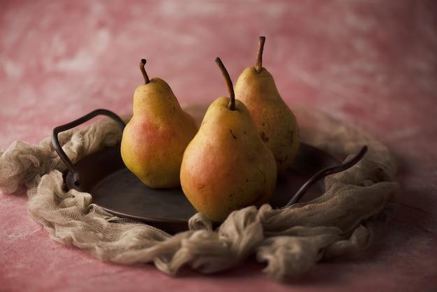 Foto de estudio de tres peras en una placa de madera