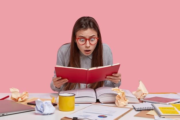 Foto de estupefacta joven trabajadora mira fijamente el bloc de notas abierto, lista de estudios para hacer el próximo fin de semana, tiene mucho trabajo, desorden en el lugar de trabajo