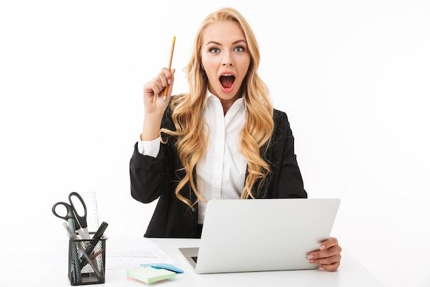 Foto de exitosa mujer de negocios sentada en el lugar de trabajo y trabajando en equipo portátil, aislado