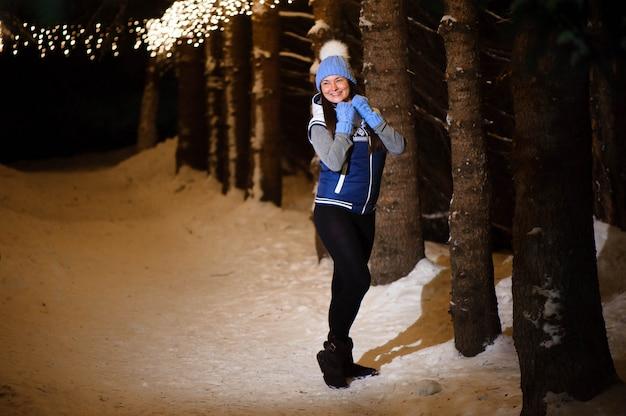 Foto exterior de joven hermosa niña sonriente feliz, posando en el callejón decorado con bombillas