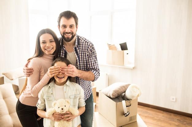 Una foto de familia agradable y alegre. los padres jóvenes sostienen sus manos sobre los ojos del niño. la pequeña niña está sosteniendo un juguete del oso y está sonriendo.