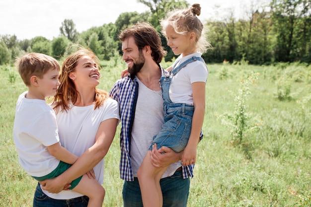 Una foto de familia amigable. el hombre y los woamn sostienen a los niños en sus manos. se miran con amor incondicional. todos estan muy felices.