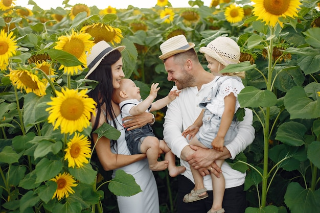 Foto de familia feliz. padres e hija. familia junta en campo de girasol. hombre con camisa blanca.