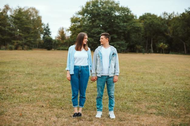 Foto de familia joven de pie en el parque tomados de la mano y mirando el uno al otro