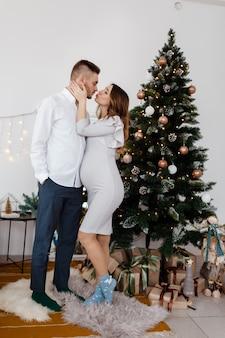 Foto de familia de navidad con adornos y árboles de navidad, piso de madera y chimenea. hombre y mujer se besan cerca de árbol de navidad.