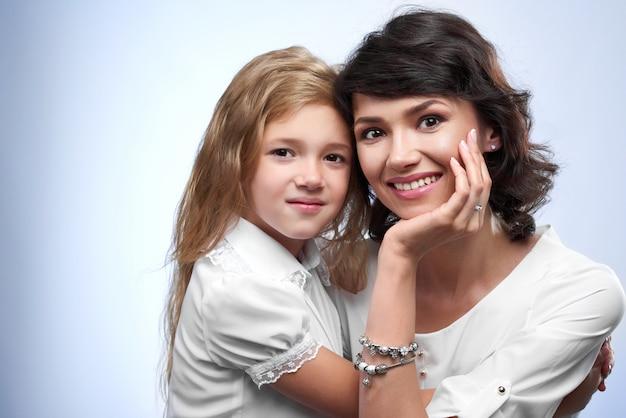 Foto de familia de una pareja feliz: sonriendo a una madre y su amada hija. son muy bonitas y simpáticas. eran camisetas blancas y se abrazan.