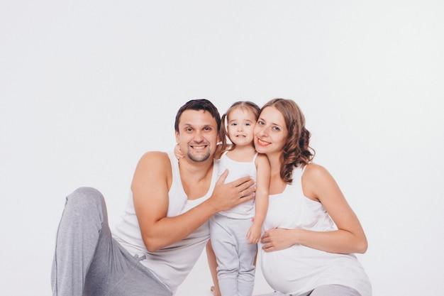Foto de familia sobre un fondo blanco, los padres pasan tiempo con sus hijos. mamá y papá abrazan al bebé.