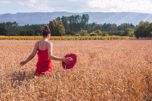 Foto fascinante de una mujer atractiva en un vestido rojo posando en un campo de trigo