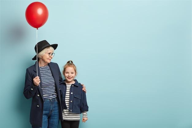 Foto de feliz abuela y nieta de pie cerca