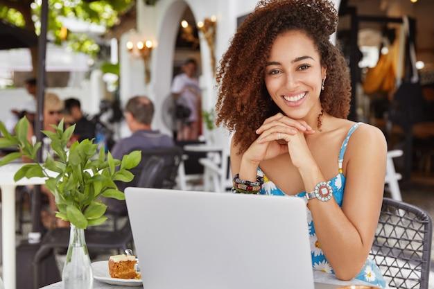 Foto de feliz adorable mujer africana rizada sentada frente a la computadora portátil abierta en la cafetería en la acera, satisfecha de hacer una buena presentación
