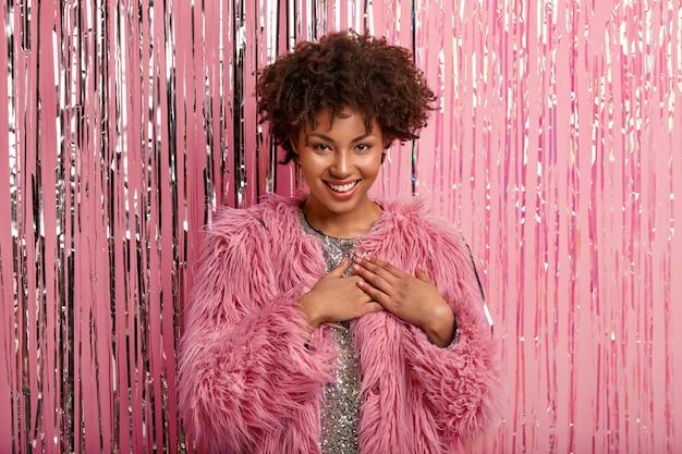 Foto de feliz mujer afro de piel oscura que mantiene ambas palmas en el pecho, expresa gratitud, usa un vestido brillante y un abrigo rosa