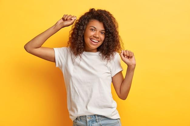 Foto de feliz mujer de cabello oscuro con expresión positiva, levanta los brazos y se mueve mientras baila, vestida con jeans y camiseta blanca casual