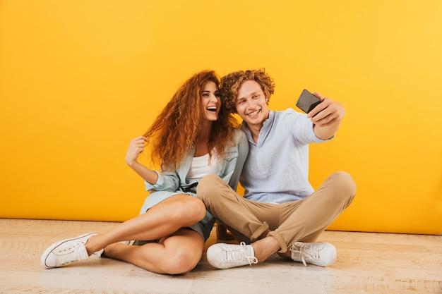 Foto de feliz novio y novia sentados en el suelo juntos y tomando selfie en smartphone, aislado sobre fondo amarillo