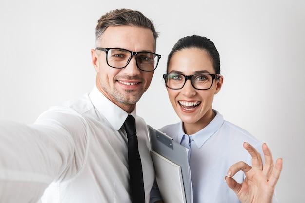 Foto de feliz pareja de colegas de negocios aislada sobre pared blanca mostrando gesto bien tomar selfie