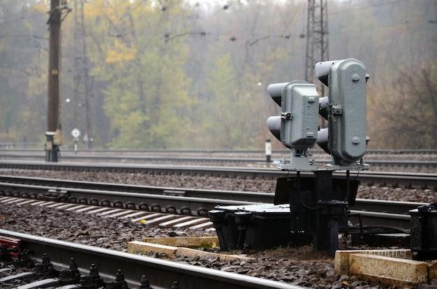 Foto de un fragmento de una vía férrea con un pequeño semáforo en tiempo lluvioso