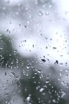 Una foto de las gotas de lluvia en el cristal de la ventana con una vista borrosa de los árboles verdes en flor