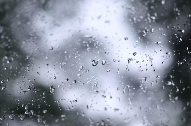 Una foto de gotas de lluvia en el vidrio de la ventana con una vista borrosa