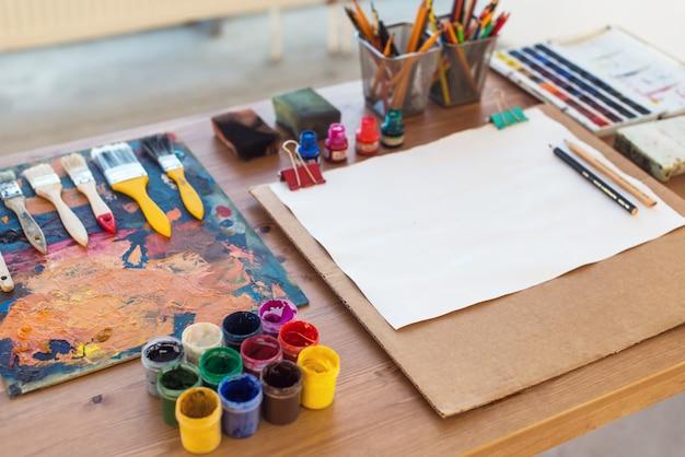 Foto de gouache y acuarela con pinceles en estudio de arte. pinturas al óleo untadas en la paleta