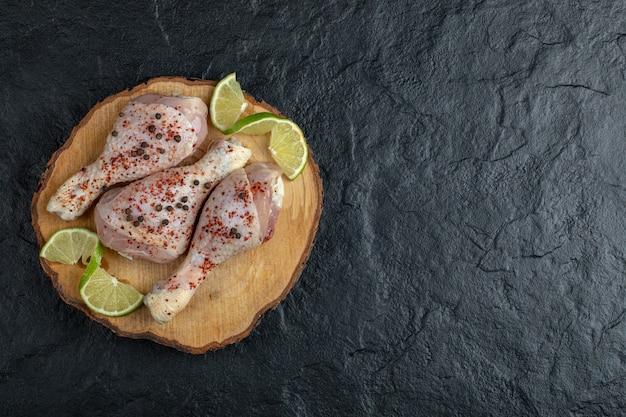 Foto de gran angular de muslos de pollo crudo marinado y verduras sobre fondo negro.