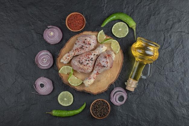 Foto de gran angular de muslos de pollo crudo y verduras sobre fondo negro.