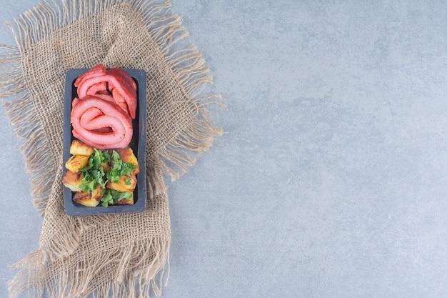 Foto granangular de tocino frito y patatas.
