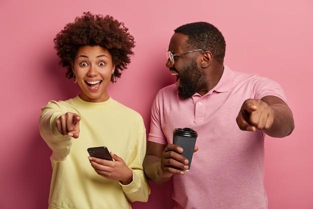 Foto de gritos emocionales femeninos y masculinos de piel oscura, mira con alegría y apunta a la cámara