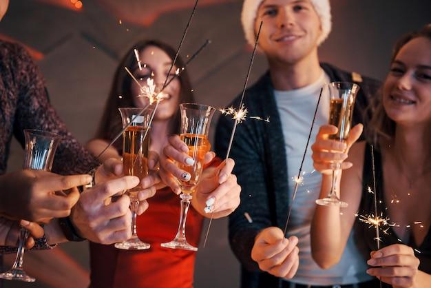 Una foto con un grupo de amigos que se divierten con muñecos de nieve y champán. feliz año nuevo. de cerca.