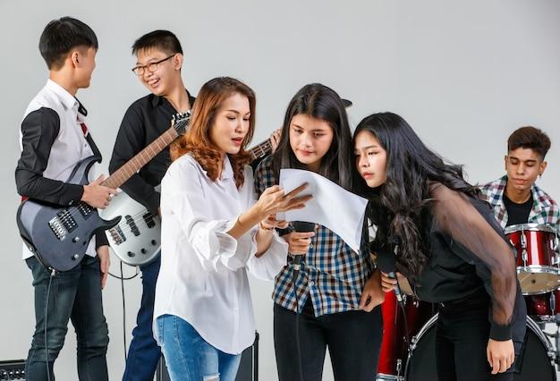 Foto de grupo de músicos adolescentes tocando la música y cantando una canción juntos. los estudiantes jóvenes tocan un instrumento. entrenadora profesional entrena a las chicas vocalistas con un músico de fondo