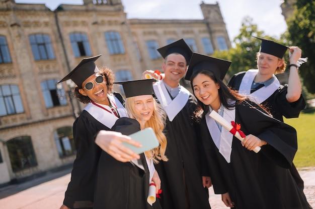 Foto de grupo. queridos compañeros de grupo parados frente a la universidad tomándose selfies después de su graduación.