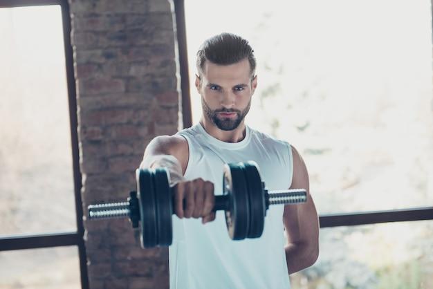 Foto de guapo chico barba caliente entrenamiento matutino músculos bíceps levantar pesas pesadas ojos tentadores mirar ropa deportiva camiseta sin mangas casa de entrenamiento grandes ventanales en el interior