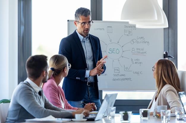 Foto de guapo empresario explicando un proyecto a sus colegas en el lugar de coworking.