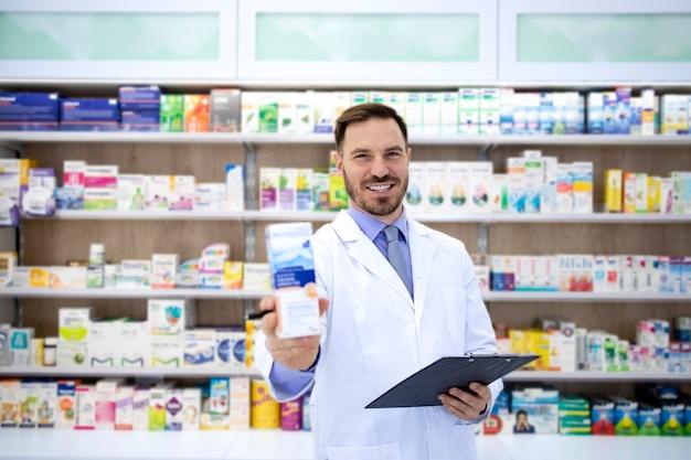 Foto de guapo farmacéutico de pie en el mostrador de la farmacia y sosteniendo vitaminas para la venta.