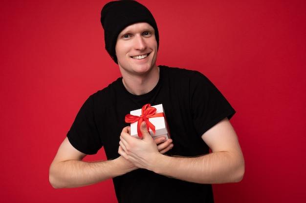 Foto de guapo joven sonriente positivo aislado sobre fondo rojo.